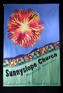 This banner representing the congregation in the Pacific Northwest Conference of the United Church of Christ, hangs in the lodge at Camp N-Sid-Sen in Idaho. The hand sun-burst is made up of hand-tracings of church participants.